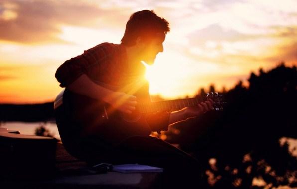Stylish boy with guitar alone